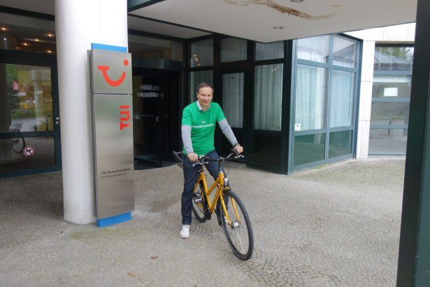 TUI Deutschland Chef Christian Clemens auf dem Fahrrad vor der TUI