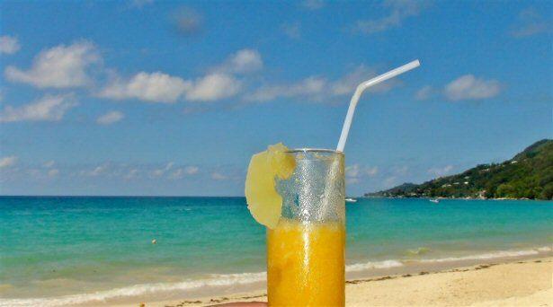 Cocktail vor türkisfarbenem Meer auf den Seychellen