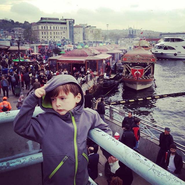Ein kleiner Junge in Kaputzen-Jacke steht an Deck einer Fähre in Istanbul