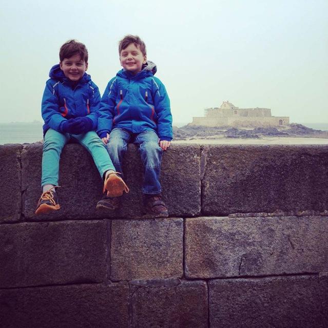 Zwei kleine Jungs in blauen Jacken sitzen auf einer Mauer in der Bretagne