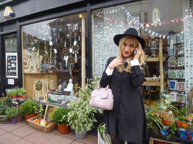 Blonde Frau im Vintage-Look steht telefonierend vor einem Shop mit Dekomaterial und Pflanzen