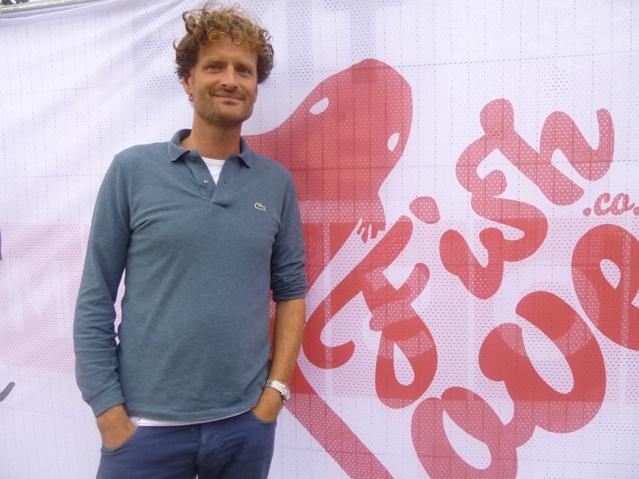 """Nicholas Röhl, blond-gelockter Mann steht vor einem Plakat auf dem in roter Schrift """"Fish Love"""" steht"""
