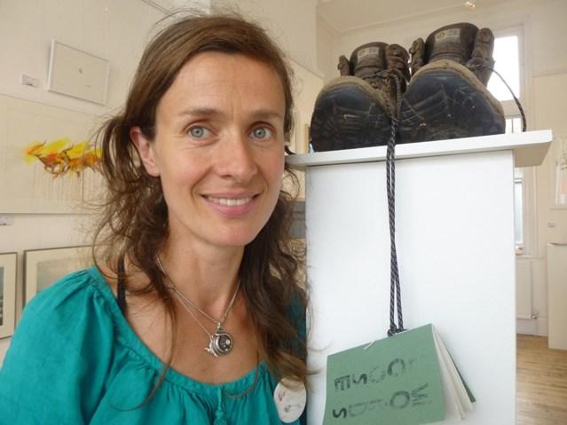 Persophone Pearl steht vor einer ihrer Installationen, einer Schuhskulptur