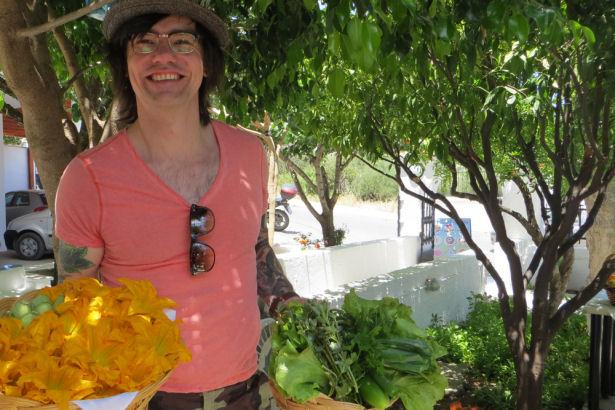 Koch Volker trägt Zucchini-Blüten in der Hand