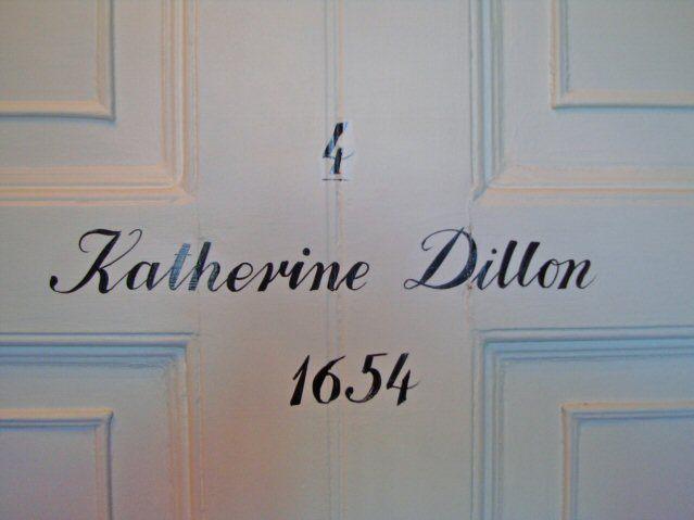 Eine weiße Hotelzimmertür mit der Aufschrift Katherine Dillon 1654