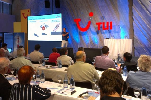 TUI-Chef Christian Clemens auf der Bühne der Pressekonferenz, im Vordergrund Tische mit Journalisten