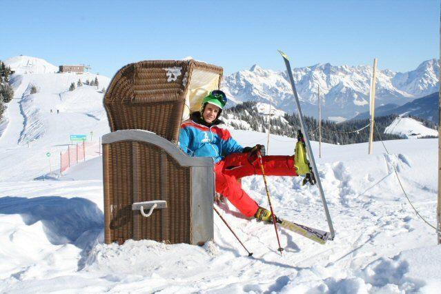 Skilehrer streckt die Beine im Skistrandkorb aus