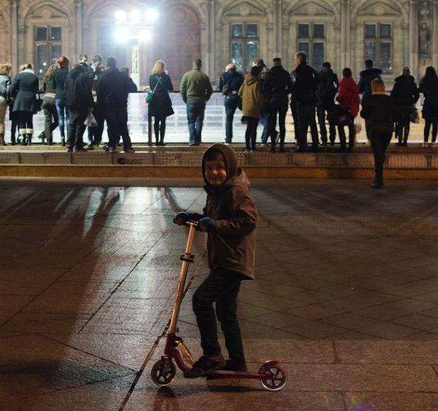 Kleiner Junge steht auf einem Tretroller vor einer Eislaufbahn