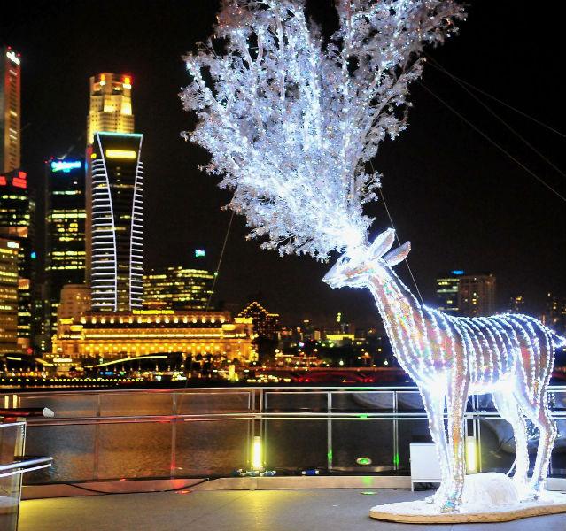 Beleuchtetes Rentier vor Fluss und Hochhäusern