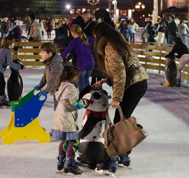 Mutter mit Handtasche und zwei Kindern auf der Eislaufbahn
