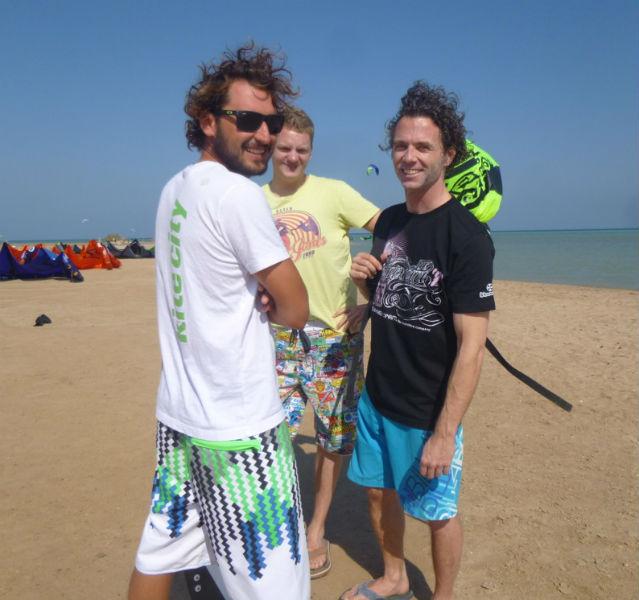 Drei Kitesurfer am Strand