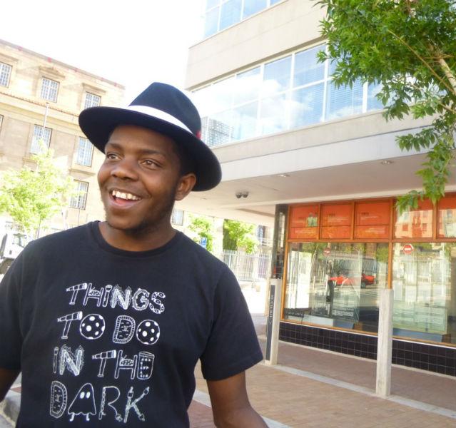 Junger Mann mit Hut vor einer ehemaligen Kanzlei