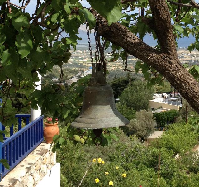 Eine Glocke hängt an einem Baum, im Hintergrund liegt ein Dorf