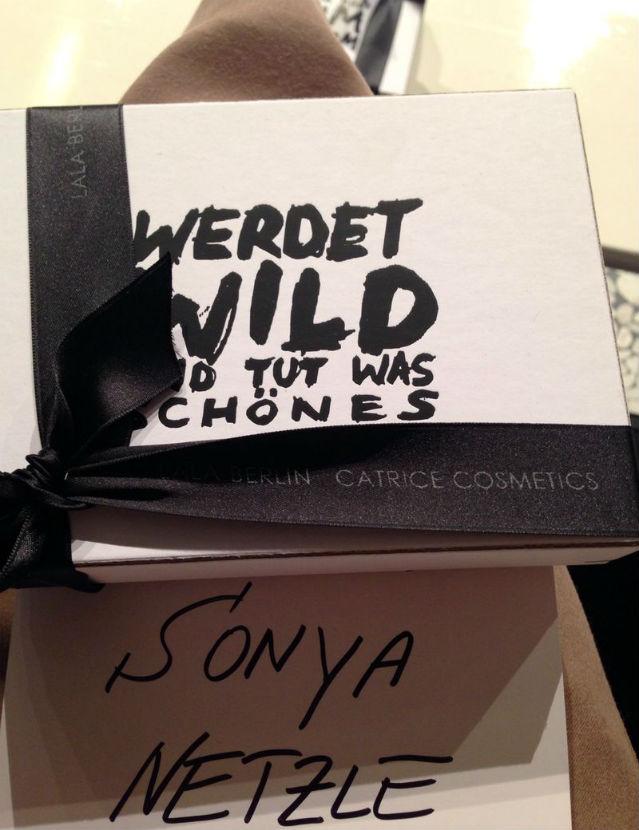 """Weißer Geschenkkarton mit schwarzer Aufschrift """"Werdet wild und tut was Schönes"""""""