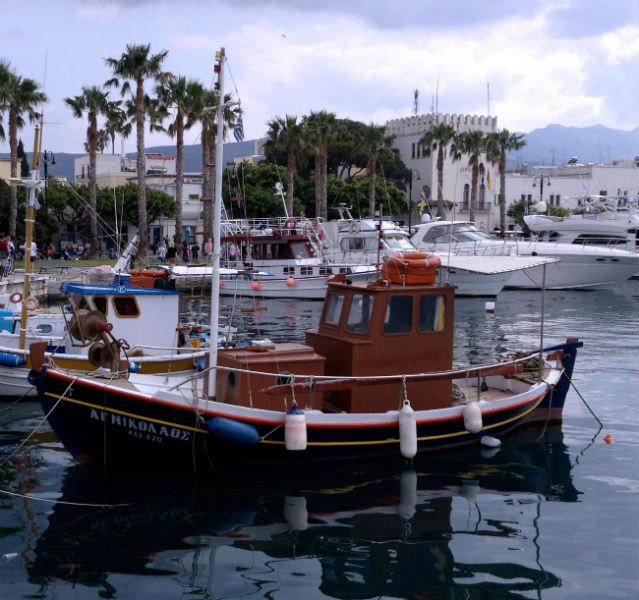 Ein rotes Boot liegt im Hafen von Kos, dahinter weitere Boote und Touristen
