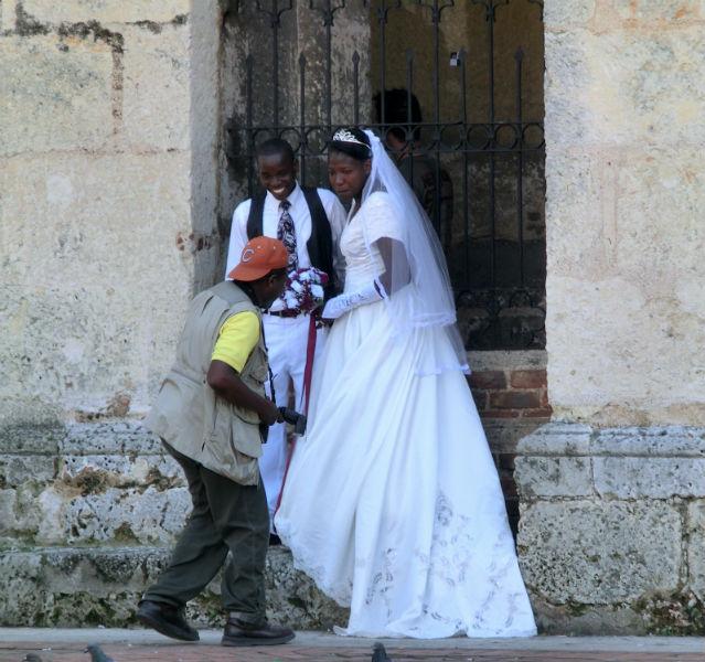 Dominikanisches Hochzeitspaar vor einer rustikalen Kirchenmauer mit einem Fotografen um Vordergrund
