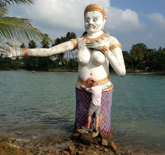 Große, füllige Frauenstatue an der Küste, die der Autor versucht zu umarmen