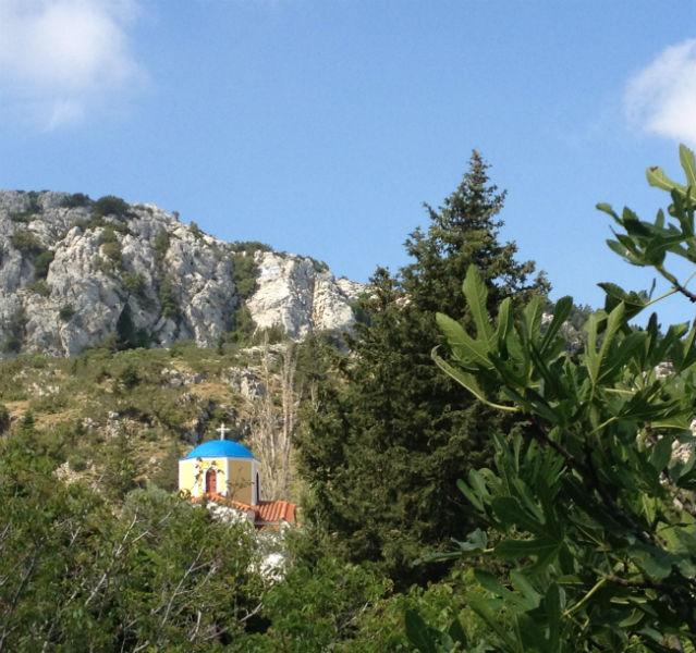 Kleine Kirche auf einem Berg, im Vordergrund Bäume und Büsche