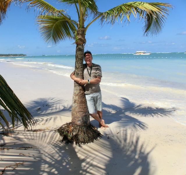 Autor Jörg Baldin unter einer Palme am Strand