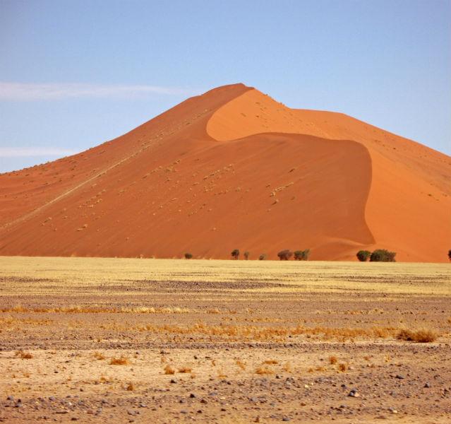 Sossusvlei ist ein Traum in Rot: Die berühmte Dünenlandschaft, wohl die älteste Wüste der Welt, ist Namibias Wahrzeichen. Die Salzpfanne des Sossusvleis bildete sich am Tsauchab-Fluss, als der versandete und eine Senke aus Salz und Lehm hinterließ. Ringsum ragen majestätisch die roten Dünen auf