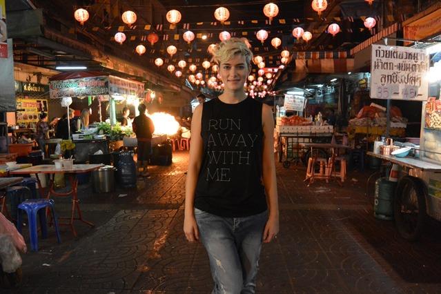 Autorin Mia Bühler steht am Abend in China Town auf der Straße, über ihr Laternen, neben ihr Marktstände