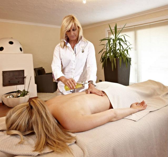Blonde Frau liegt auf einer Massageliege, eine andere blonde FRau gießt Öl aus einer Flasche auf ihren Rücken