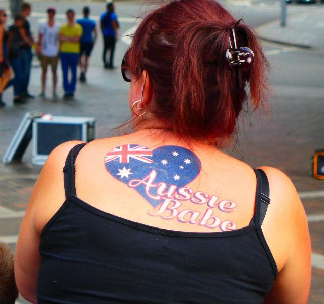 Frau mit Aussie Babe Tattoo auf dem Rücken