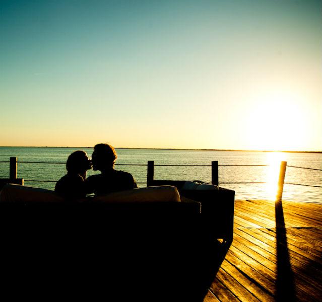 Paar sitzt auf der Terrasse mit Sonnenuntergang