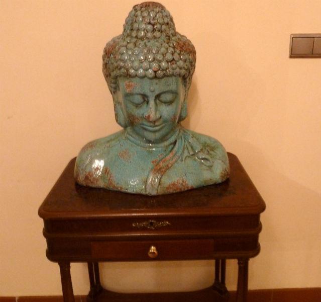 Grüne Buddha-Kopf-Statue auf einem braunen Tisch