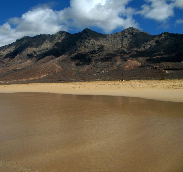 Strand mit dunklen Hügeln im Hintergrund