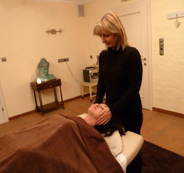 Dagmar Gehm liegt auf der Massageliege unter einer braunen Decke und wird im Gesicht massiert