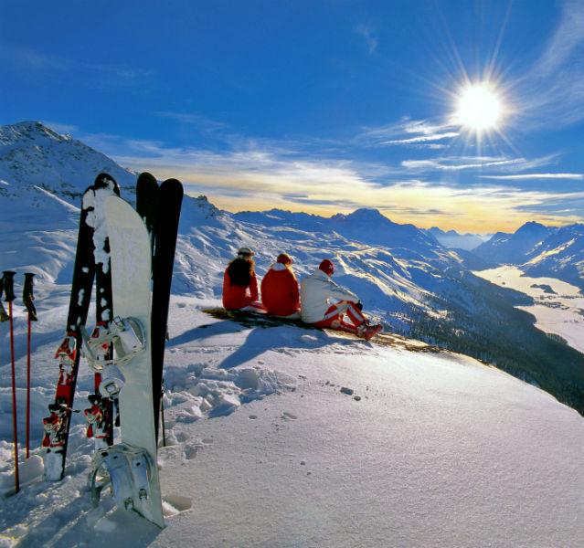 Skifahrer sitzen auf einem Berg und schauen in den Sonnenuntergang