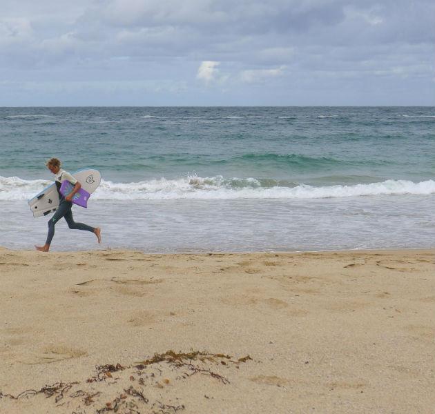 Surfer rennt am Strand
