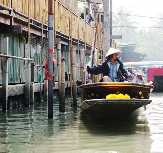 Wie in Venedig schippern die Thai-Boote an Pfählen und Häusern im Wasser vorbei