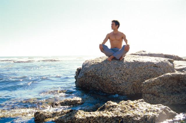Mann meditiert auf Stein - Yogaurlaub am Meer