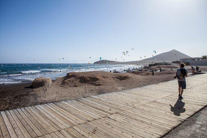Strandpromenade mit Windsurfern im Hintergrund