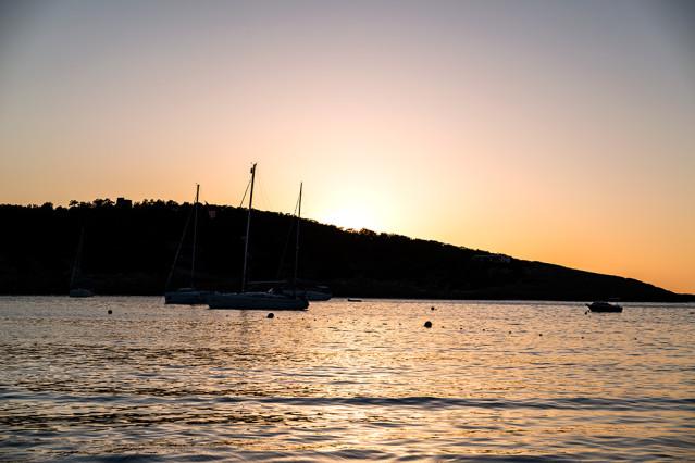 Blick au den Hafen von Portinatx vor der untergehenden Sonne.