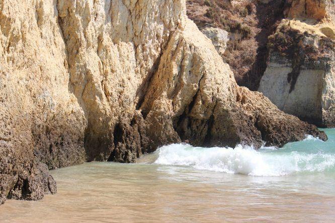 Wellen schlagen gegen die Felsen an der Praia dos Três Irmãos