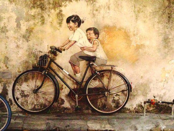 Streetart von Ernest Zacharevic: Zwei Kinder beim Fahrradfahren