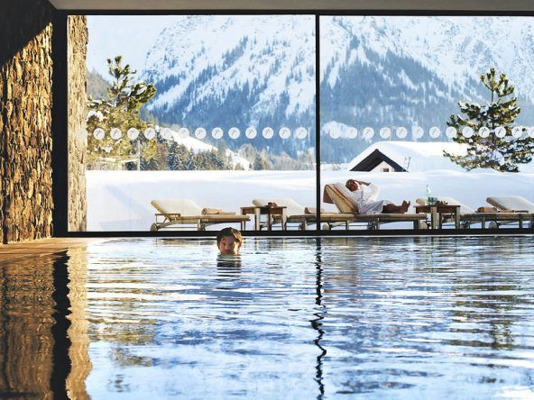Im Travel Charme Ifen Hotel gibt es einen 18-Meter-Innenpool mit bestem Blick auf die verschneite Bergwelt