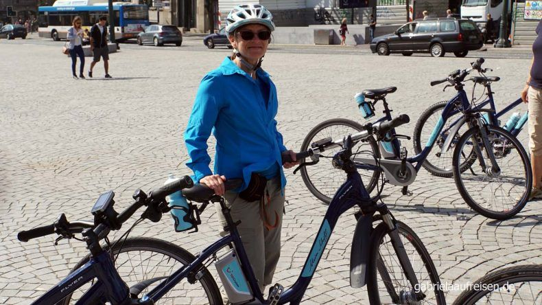 Gabriela steht mit dem E-Bike auf dem Rathausplatz in Porto.