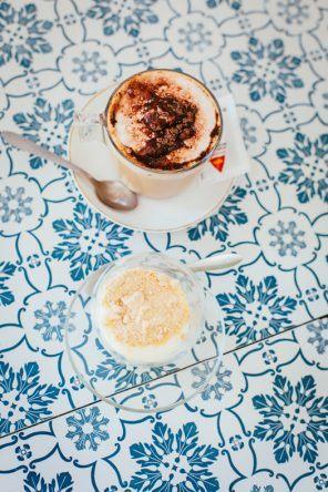 Kaffee und weiße Milchcreme mit Kekskrümeln im Café com Calma (Fotocredit: Thea Neubauer)