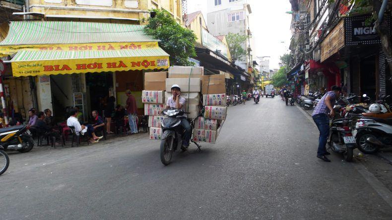 Ein voll beladener Mopedfahrer mit offenen Helm und Telefon am Ohr