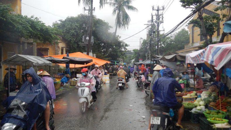 Mit Regencapes schützen sich die Rollerfahrer vor dem Regen während sie auf dem Markt einkaufen