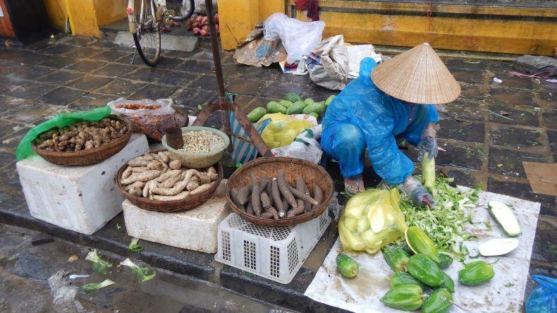 Papaya und Wurzelgemüse wird von dem Verkäufer geschält und vorbereitet