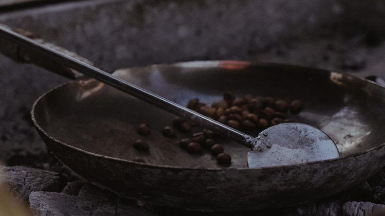 Kaffeebohnen werden über dem offenen Feuer geröstet.
