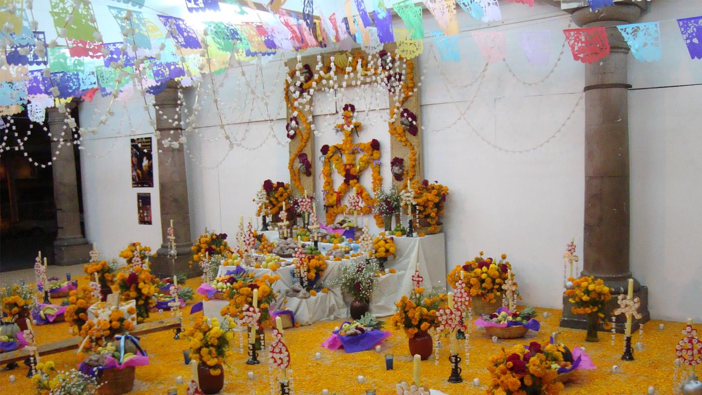 Papiergirlanden, Kerzen, Blumen und Ofrendas. Die Gräber und Altare werden reich geschmückt.