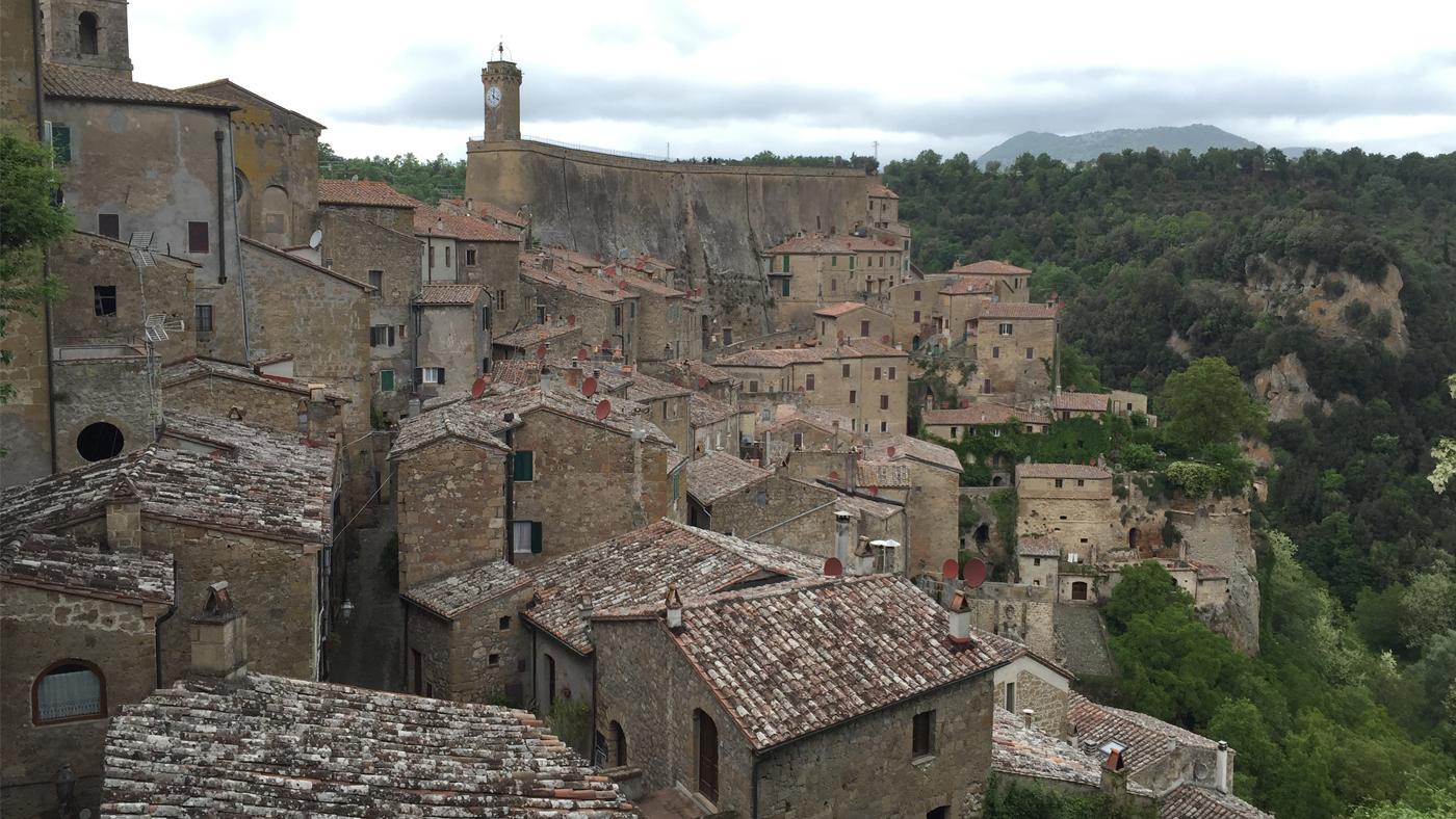 Die mittelalterlichen Gebäude sind eng an den Hang des Tuffsteinmassivs gebaut worden.