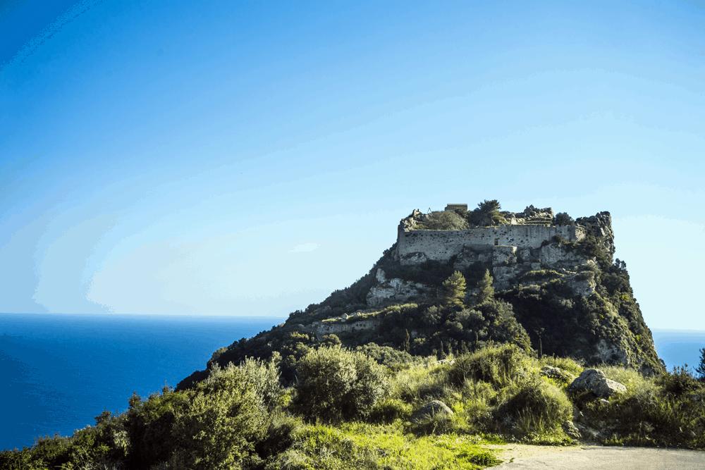 Hoch auf einem Felsen erhebt sich die monumentale Ruine von Angelokastro über die Adria
