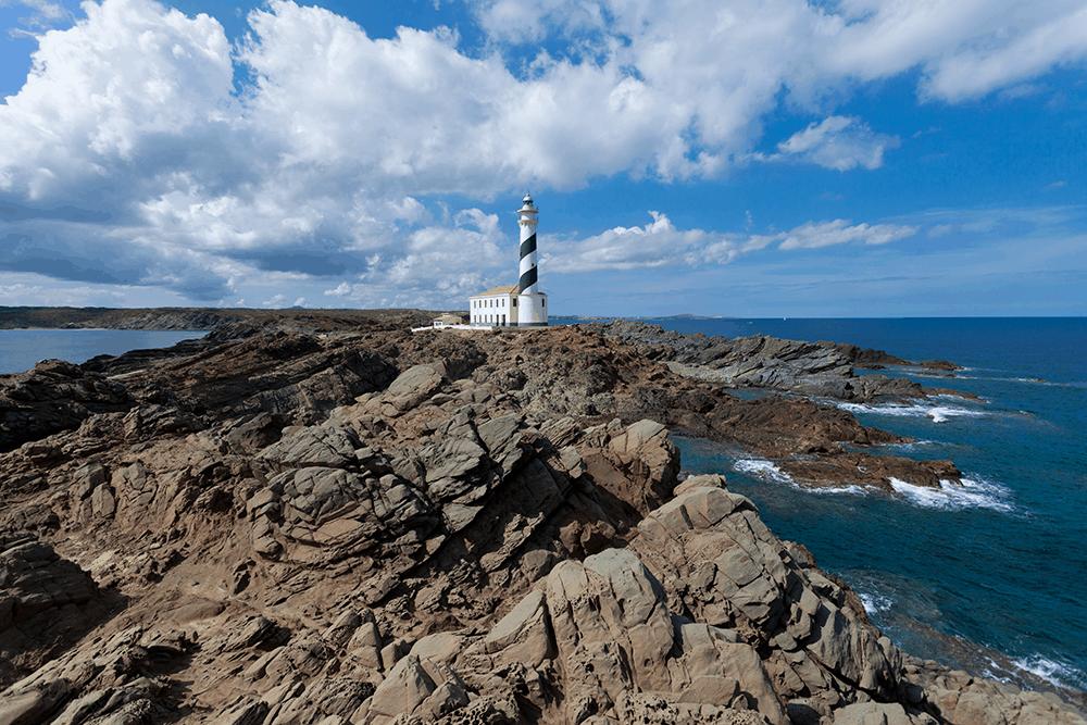 An der Ostküste Menorcas erwartet dich Faro de Favaritx, ein ungewohnt düsterer und doch zugleich faszinierender Anblick: Karges Schiefergestein bildet eine dunkle, zerklüftete Landschaft
